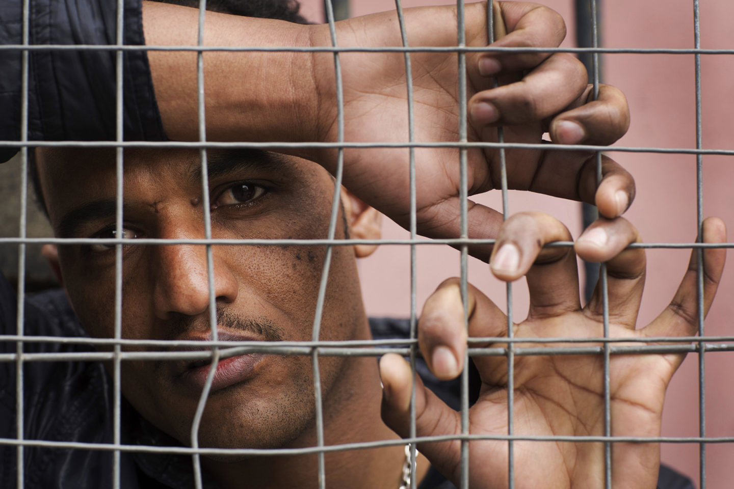 Eritrean refugee in Glasgow behind a fence