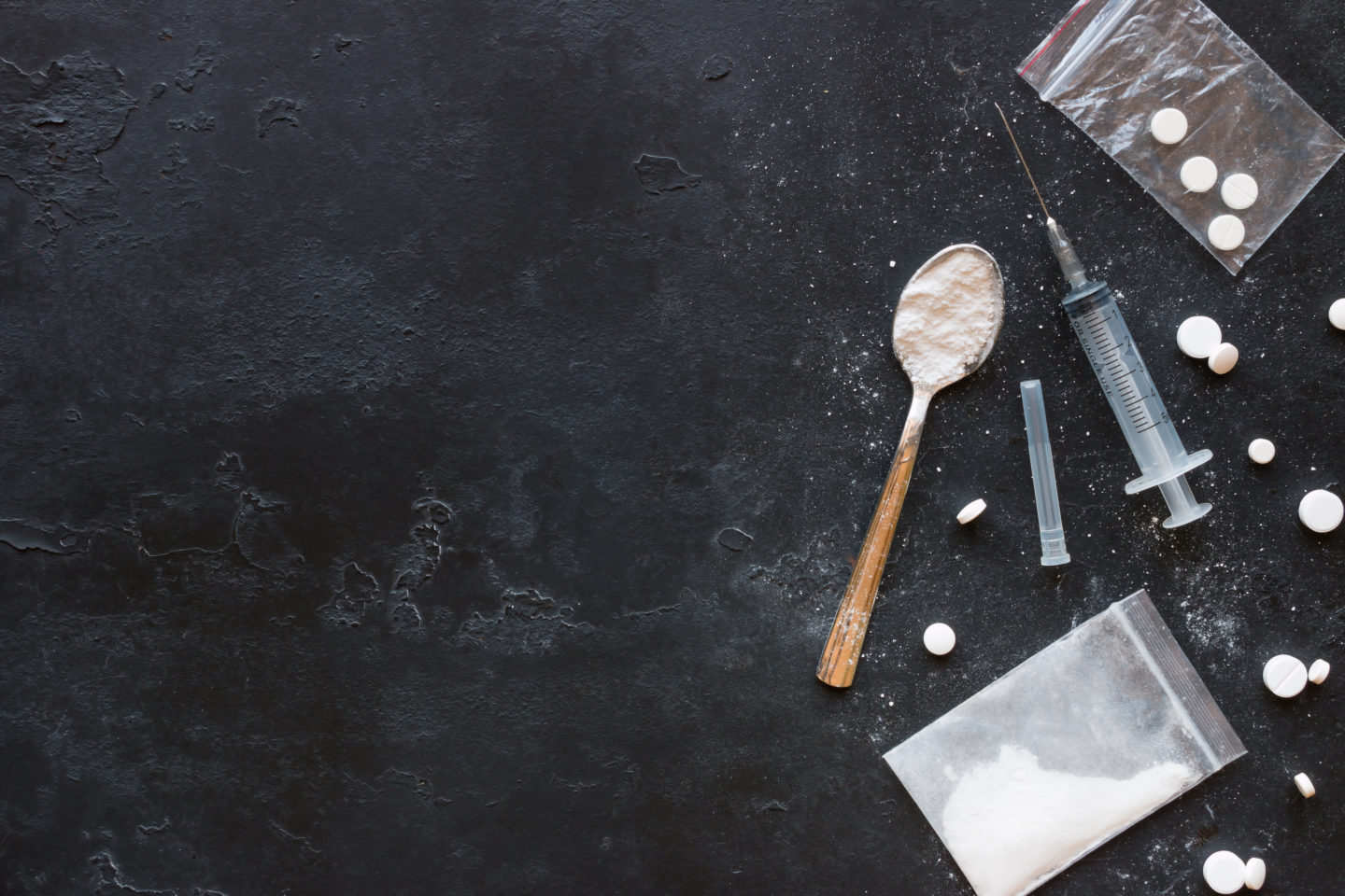 Drugs in the form of powder and tablets, a spoon and a syringe